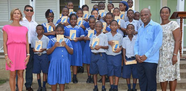Christina and Aron Truss (left), along with teacher Sandra Cumberbatch and parliamentary representative Edmund Hinkson (right) flank St Alban's Class Three pupils who show off their new tablets.