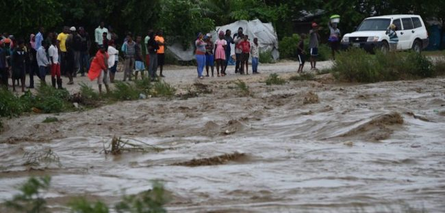 People watch from the other side of the La Digue River as water roars past the destroyed Petit Goave bridge. (AP Photo/Dieu Nalio Chery)