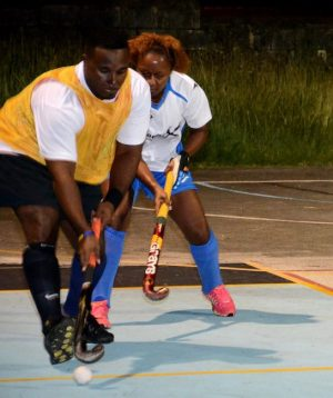 Barbados Hockey Federation secretary, Kofi Hinds of ROGCOL Royals (in bib) under the watchful eye of ex-national stalwart Maria Sealy of Legends in their 6-6 thriller Sunday. (Photos by Maynard2 Photography)