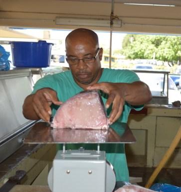 Curwen Brewster weighs fish for a customer.