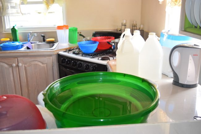 Plastic containers are the order of the day for this resident who has been without running water flowing through her tap for over a week.