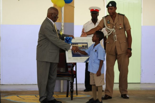 Deputy head boy Kemani Mayers warmly shakes the hands of the Governor General as he presents a special gift to the Head of State.