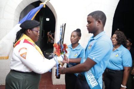 Shawné Mayers hands over the Broken Trident to St Joseph Parish Ambassadors Cadesha Rowe and Brandon Beckles.