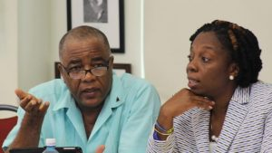 General Secretary of the Unity Workers Union Caswell Franklyn (left) in discussion with General Secretary of the Barbados Workers' Union (BWU) Toni Moore at Monday morning's conference.