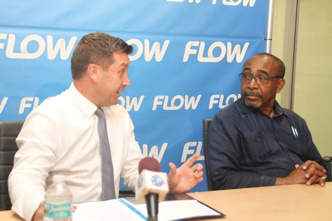 Senator Darcy Boyce engages Managing Director of Flow Barbados Niall Sheehy (standing) and Sharon Jemmott, head of products, Flow.