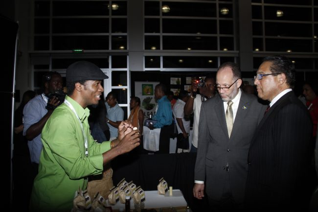 Haitian Jean-Sebastien Duvilaire (left) Tahomey Chocolate Company, shows off one of his products to CARICOM Secretary General Ambassador Irwin LaRocque (centre) and Premier of the Cayman Islands Alden McLaughlin at Caribbean Week of Agriculture 2016.