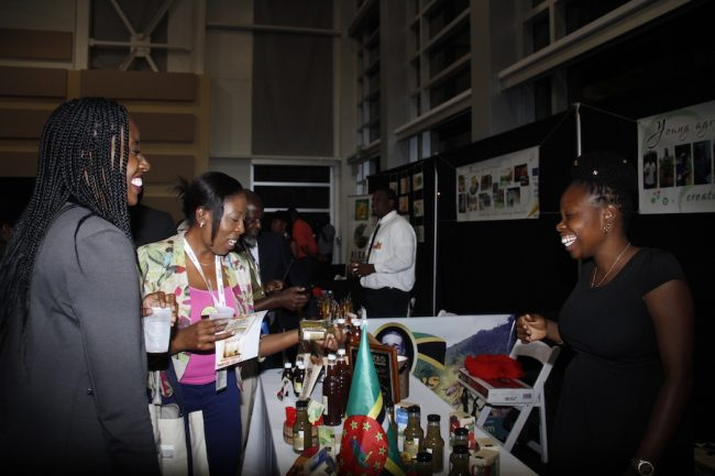 Dominican entrepreneur Kamarsha Sylvester (right), owner of Taste of Eden, shares a light moment with attendees at Caribbean Week of Agriculture 2016 Agriculture MarketPlace in Grand Cayman.