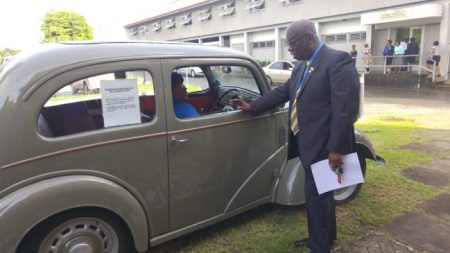 Chief Education Officer Karen Best in the driver's seat of a 1940 Ford Popular while Minister of Education Ronald Jones looks on. The vintage car was part of the presentation from the Education Project Implementation Unit.