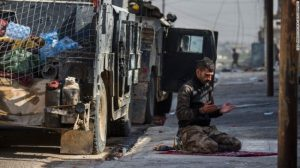 An Iraqi special forces soldier prays next to a Humvee before troops pushed towards Mosul's Karkukli neighbourhood.