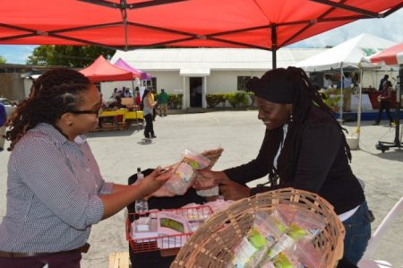 Ifill explains the benefits of green bananas to a member of the public at this year's World Food Day activities.