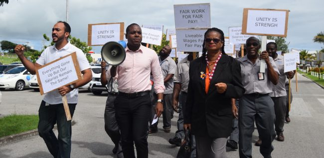 From left, the NUPW's Treasurer Asokore Beckles, President Akanni McDowall and General Secretary Roslyn Smith leading workers at Grantley Adams International Airport in industrial action today.