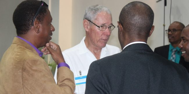 Businessman Ralph Bizzy WIlliams (centre) in discussion with other delegates at today's energy conference.