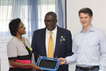 Principal of the Maria Holder Gall Hill Nursery School Olwin Walker receives her iPad from Parliamentary Secretary in the Ministry of Education Senator Harcourt Husbands and Alex Eiden of Khan Academy.