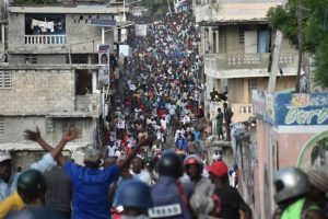 Supporters of one of the candidates, Maryse Narcisse, march to claim her victory, demonstrators have led violent protests on the streets of the capital.