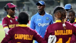 Vasbert Drakes with members of the West Indies Women's team.