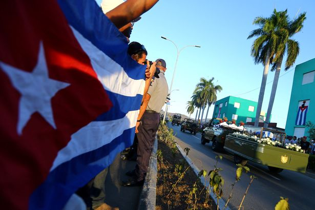 people-watch-the-cortege-carrying-the-ashes-of-cubas-former-president-fidel-castro-drive-toward-san
