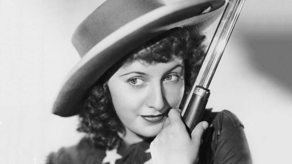 Barbara Stanwyck poses with a rifle as the iconic Annie Oakley in a publicity still of the same name. Annie Oakley ranks 18 of Barbara Stanwyck movies list.
