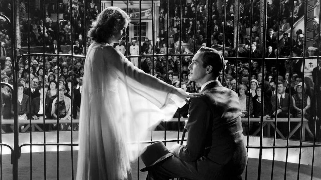 Barbara Stanwyck playing fake evangelist Floren Fallon in a scene of the movie, inside a lion's cage with David Manners. The Miracle Woman makes it to Stanwyck's best movies list.