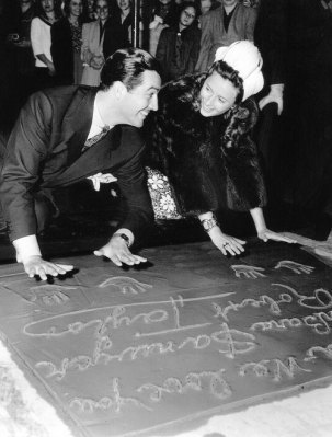 Barbara Stanwyck Biography: with Robert Taylor immortalizing foot and hand print at Graumann's Theater. You can still visit those today.