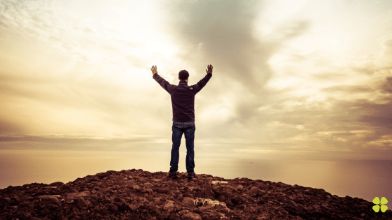 5 keys to trauma recovery man standing on a mountain with arms outstretched to the golden sky