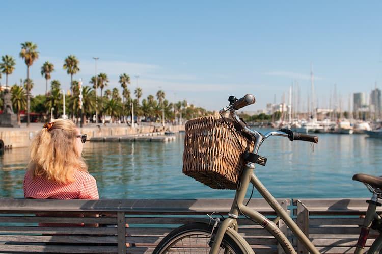 Fiets en vrouw op bankje aan haven in Barcelona