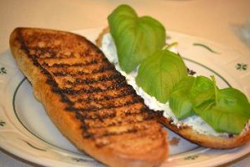 Grilled_bread_with_goat_cheese_and_basil_leaves._small