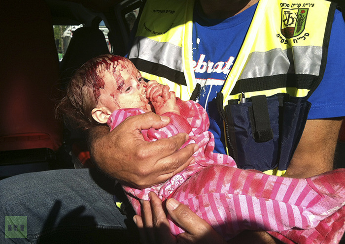 An injured Israeli baby is held by a security officer inside an ambulance at the scene where a rocket, fired from Gaza, landed in Kiryat Malachi