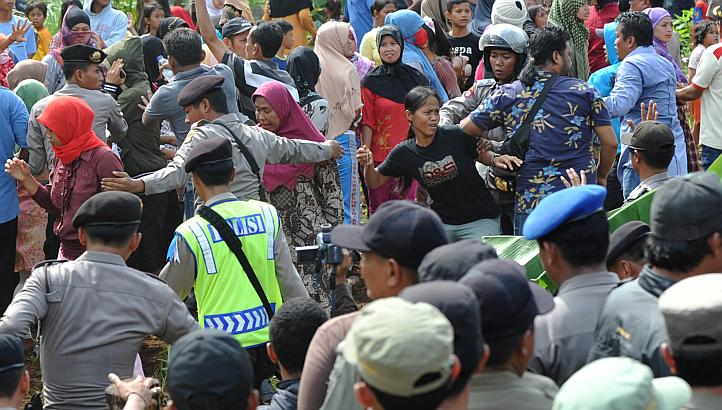 Indonesian police block angry Muslim residents away from Christian worshippers from the Filadelfia Batak Christian Protestant intent on holding a Christmas mass on their property at the Jejalen Jaya village in Bekasi on Dec 25, 2012. More than 200 Indonesian Muslims threw rotten eggs at Christians wanting to hold a Christmas mass near land outside Jakarta where they plan to build a church