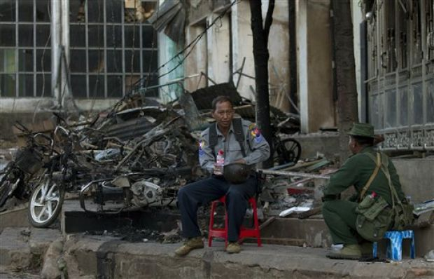 A policeman and an army officer guard a burned mosque in Lashio