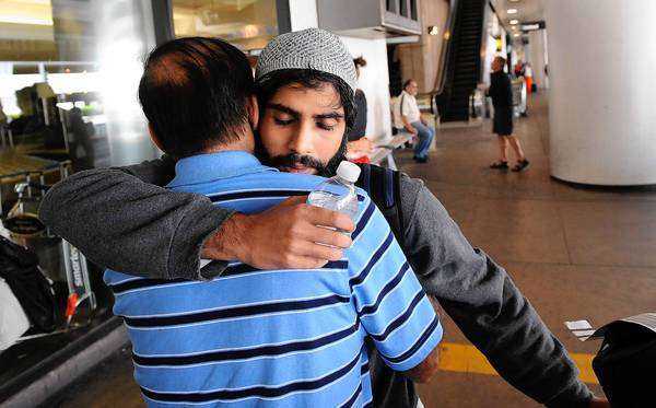 Rehan Motiwala hugs his father, Rafiq, upon arrival at LAX after a 10-day detention at the Bangkok airport