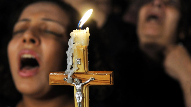 Egyptian Coptic Christians carry a cross and chant prayers during a candlelight protest marking one week since sectarian clashes with soldiers and riot police at a protest against an attack on a church in southern Egypt, at Abassaiya Cathedral in Cairo