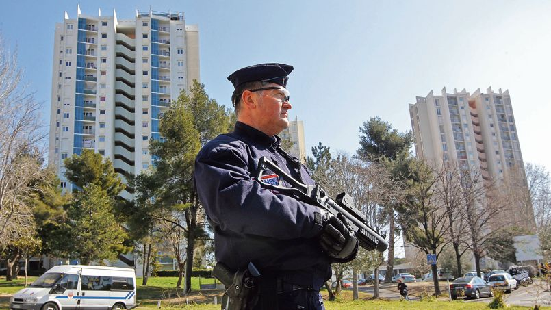 French policeman stands guard during a control operation in apartment housing buildings at Air-Bel in Marseille
