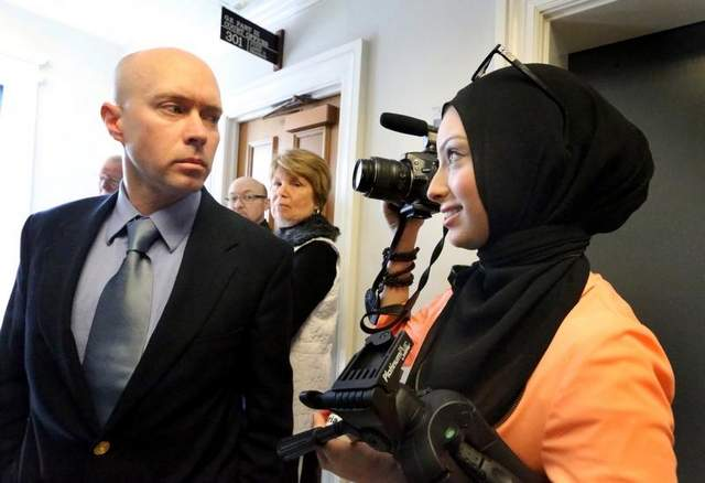 Micah Forrest,left, stares down and blocks Maryland University Journalism student Noor Tagouri from filming outside the courtroom of Chancellor Robert Corlew III, after Corlew excuses himself from the court case challenging the Islamic Center of Murfreesboro cemetery approval by the Rutherford County Board of Zoning Appeals