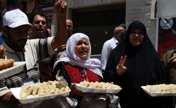 Women handing out sweets in Gaza City