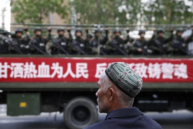 662285-a-uighur-man-looks-on-as-a-truck-carrying-paramilitary-policemen-travel-along-a-street-during-an-ant