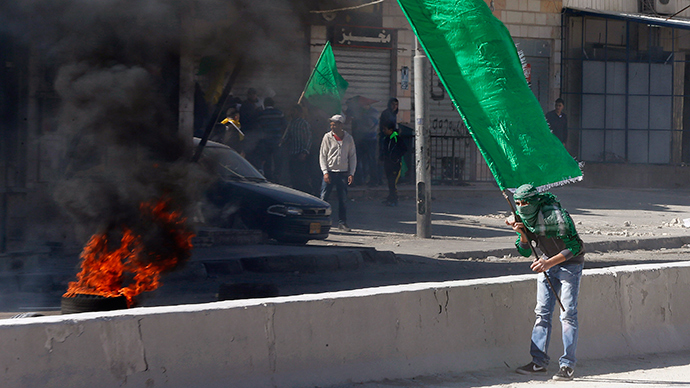 A Palestinian protester holds a Hamas flag during clashes with Israeli troops following a protest against what organizers say are recent visits by Jewish activists to al-Aqsa mosque
