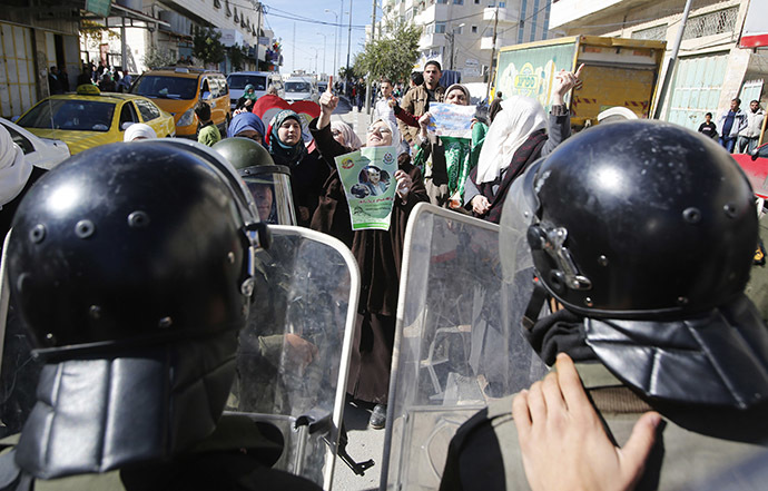 Members of Palestinian security forces take position as Palestinian women take part in an anti-Israel protest against what organizers say are recent visits by Jewish activists to al-Aqsa mosque