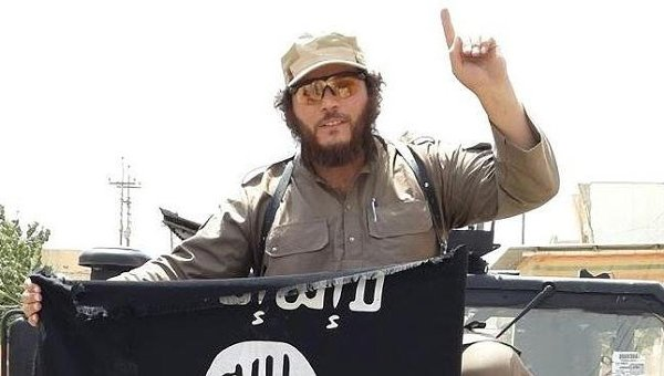 ISIS jihadist with ISIS flag and one-finger ISIS salute