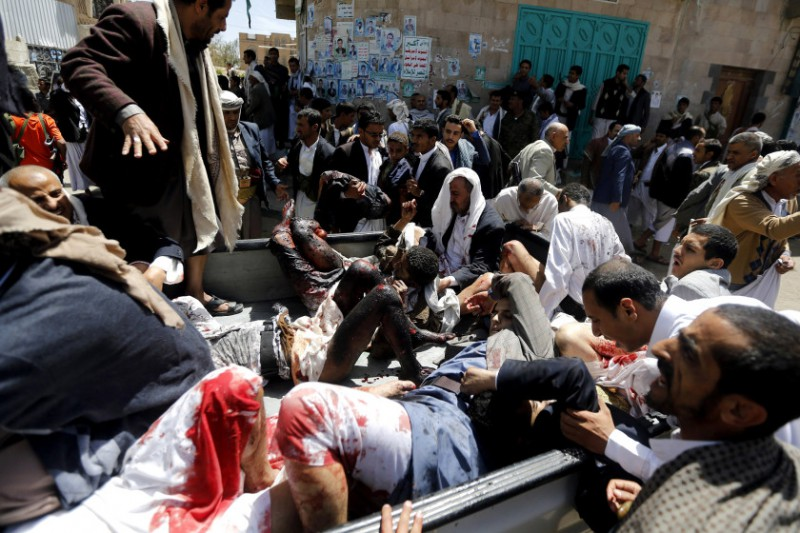 Injured people are carried onto a truck to be rushed to a hospital after a suicide bomb attack at a mosque in Sanaa