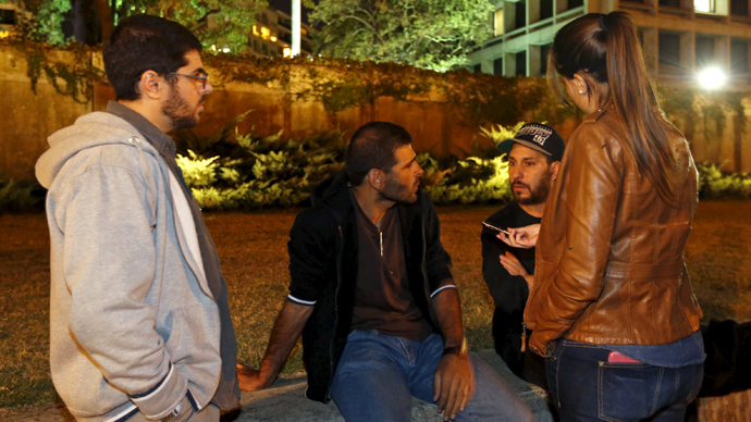 Ex detenidos de Guantánamo Omar Mahmoud Faraj (L), Ali Shabaan (C) y Abdul din Muhammed Cuentos (segundo R) frente a la embajada de Estados Unidos en Montevideo