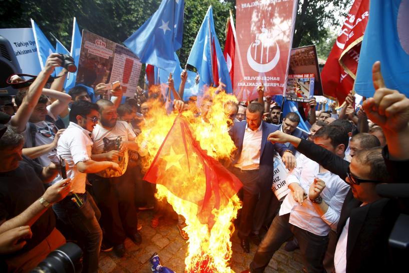 Demonstrators set fire to a Chinese flag during a protest against China near the Chinese Consulate in Istanbul, Turkey