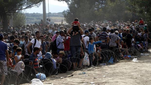 Invaders stand behind the barbed wire set by Macedonian police to stop thousands of migrants entering Macedonia illegally from Greece