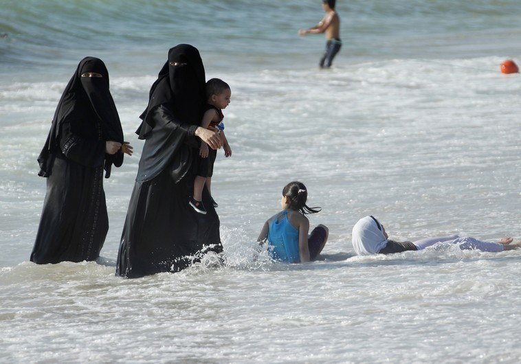 Veiled women, with their children, enjoy the warm weather on a beach at the port city of Sidon in southern Lebanon