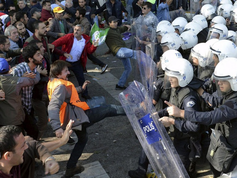 Demonstrators confront riot police following explosions during a peace march in Ankara,