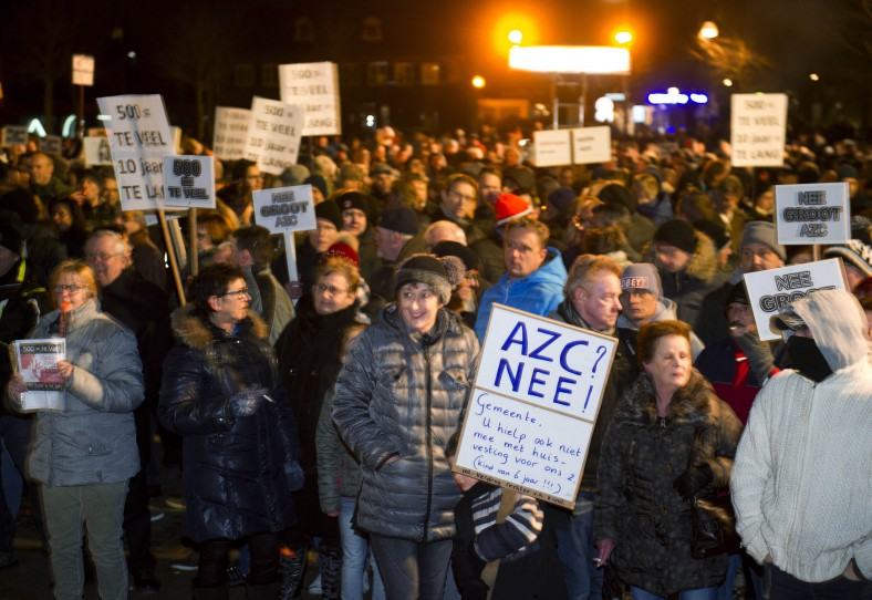 A child can be seen holding a sign in Dutch. It reads in English: Asylum Center No! Council: You won't help us with our own housing…""