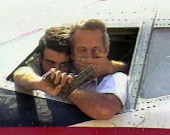 TWA captain John L. Testrake in the cockpit of his hijacked airliner at Beirut airport while a Shia Muslim terrorist (background) holds him at gunpoint.