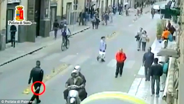 CCTV footage showed gang leader Emanuele Rubino apparently retrieve a handgun (circled) before shooting Gambian Yusapha Susso