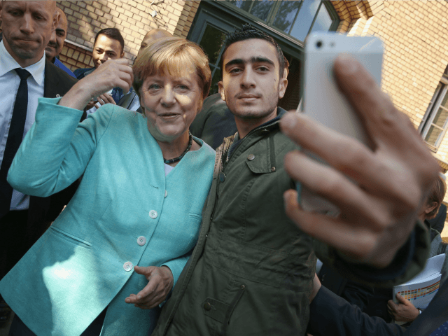 German-Chancellor-Angela-Merkel-poses-for-a-selfie-with-a-migrant-from-Syria-after-she-visited-the-AWO-Refugium-Askanierring-shelter-for-migrants-Getty-640x480