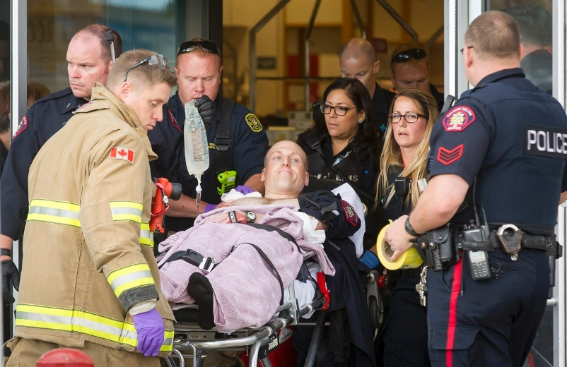 A police officer is wheeled on a stretcher out of the Sears in Marlborough Mall in Calgary, Alta., on Saturday, Sept. 17, 2016.