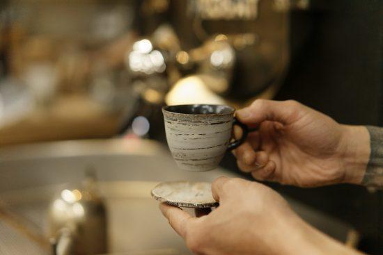 Un primer plano de una mano sosteniendo una taza de cerámica.